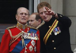 ASSOCIATED PRESS / 2014                                 Britain's Prince Harry talks to Prince Philip as members of the Royal family appear on the balcony of Buckingham Palace, during the Trooping The Colour parade, in central London. Buckingham Palace officials say Prince Philip, the husband of Queen Elizabeth II, has died. Prince Harry, Philip's grandson who stepped away from royal duties last year and now lives in California, will attend the service along with other members of the royal family.
