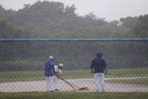 JAMM AQUINO / JAQUINO@STARADVERTISER.COM                                 Kailua High School baseball coaches tend to a flooded field as this afternoon's OIA baseball game against the Kalani Falcons was called off due to the weather.
