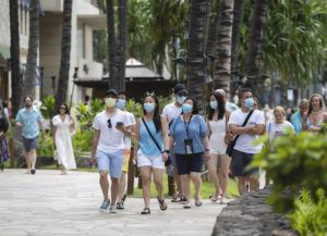 CINDY ELLEN RUSSELL / MAY 25                                 Pedestrians wear masks as they walk along Kalakaua Avenue in Waikiki. Wearing masks outdoors is no longer required by the state, Gov. David Ige announced on Tuesday.
