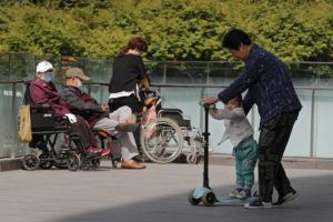 ASSOCIATED PRESS                                 A woman plays with a child near elderly people on wheelchairs sunbathing on a compound of a commercial office building in Beijing on Monday.