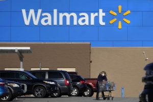 ASSOCIATED PRESS / 2020                                 A woman, wearing a protective face mask due to the COVID-19 virus outbreak, wheels a cart with her purchases out of a Walmart store, in Derry, N.H.