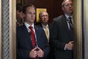 ASSOCIATED PRESS                                 Senate Minority Leader Mitch McConnell of Ky., center, takes an elevator, today, after a meeting with Senate Republicans on Capitol Hill in Washington.