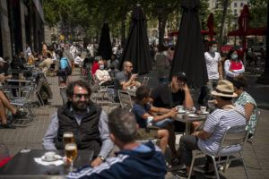 ASSOCIATED PRESS                                 Customers sit in a terrace bar in downtown Barcelona, Spain, on Friday.