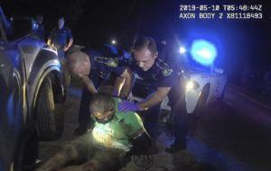 LOUISIANA STATE POLICE VIA ASSOCIATED PRESS                                 This screenshot from Louisiana state police state trooper Dakota DeMoss' body-worn camera, shows troopers holding up Ronald Greene before paramedics arrived in May 2019, outside of Monroe, La. The video obtained by The Associated Press shows Louisiana state troopers stunning, punching and dragging the Black man as he apologizes for leading them on a high-speed chase, footage authorities refused to release in the two years since Greene died in police custody.