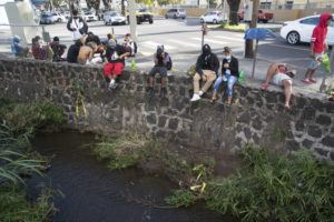 GEORGE F. LEE / APRIL 7                                 Mourners of 16-year-old Iremamber Sykap, who was shot by police, gathered at the corner of Kalakaua Avenue and Philip Street at the canal where Sykap was shot.