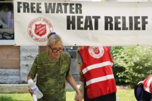 ASSOCIATED PRESS                                 A pedestrian takes a bottle of water at a Salvation Army hydration station during a heatwave as temperatures hit 115-degrees today in Phoenix.