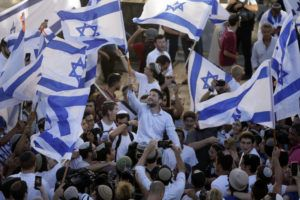"""ASSOCIATED PRESS                                 Israeli Knesset members Bezalel Smotrich, center, waves an Israeli flag together with other Jewish ultranationalists during the """"Flags March"""" next to Damascus gate, outside Jerusalem's Old City, Tuesday."""