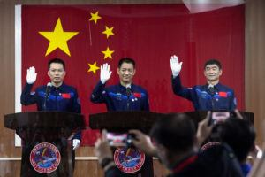 ASSOCIATED PRESS                                 Chinese astronauts, from left, Tang Hongbo, Nie Haisheng, and Liu Boming wave at a press conference at the Jiuquan Satellite Launch Center ahead of the Shenzhou-12 launch from Jiuquan in northwestern China, Wednesday.
