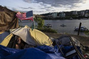 """ASSOCIATED PRESS                                 Frank, a homeless man sat in his tent with a river view in Portland, Ore., on June 5. Until a year ago, the city was best known nationally for its ambrosial food scene, craft breweries and """"Portlandia"""" hipsters."""