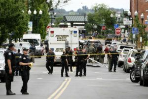 COURTESY THE DENVER POST VIA AP Police officers investigate the scene of an early afternoon shooting in Olde Town Arvada today, in Arvada, Colo.