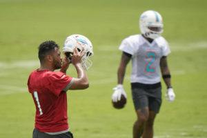 ASSOCIATED PRESS                                 Miami Dolphins quarterback Tua Tagovailoa takes off his helmet between drills during a mandatory minicamp on Tuesday.