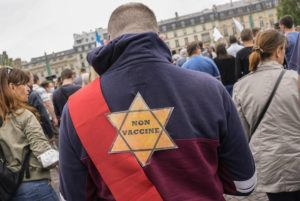 """ASSOCIATED PRESS                                 A star that read """"NOT VACCINATED"""" was attached to the back of an Anti-vaccine protester during a rally in Paris, Saturday. A Holocaust survivor, French officials and anti-racism groups are denouncing anti-vaccination protesters who are comparing themselves to Jews persecuted by the Nazis."""