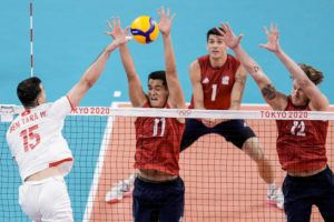 ASSOCIATED PRESS                                 Kamehameha alumnus Micah Christenson, second left, and United States' Maxwell Holt, right, block the ball during a men's volleyball preliminary round pool B match between United States and Tunisia at the 2020 Summer Olympics, Wednesday, in Tokyo, Japan.