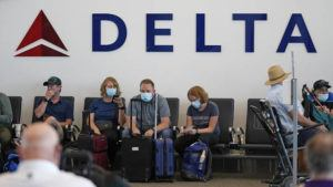 ASSOCIATED PRESS                                 People sat under Delta sign at Salt Lake City International Airport, July 1, in Salt Lake City. Delta Air Lines won't force employees to get vaccinated, but it's going to make unvaccinated workers pay a $200 monthly charge.