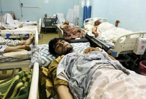 ASSOCIATED PRESS                                 Wounded Afghans lie on a bed at a hospital after a deadly explosions today outside the airport in Kabul, Afghanistan.