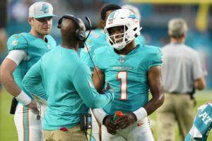 ASSOCIATED PRESS                                 Miami Dolphins quarterback Tua Tagovailoa (1) talked to head coach Brian Flores during the first half of a preseason football game against the Atlanta Falcons, Saturday, in Miami Gardens, Fla.