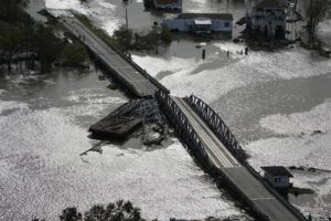 ASSOCIATED PRESS                                 A barge damages a bridge that divides Lafitte, La., and Jean Lafitte, in the aftermath of Hurricane Ida, today.