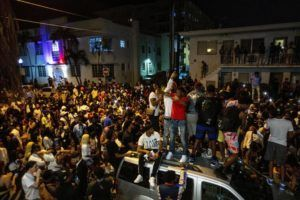 DANIEL A. VARELA/MIAMI HERALD VIA AP / MARCH 21                                 Crowds defiantly gather in the street while a speaker blasts music an hour past curfew in Miami Beach, Fla. South Beach's sizzling party scene is about to undergo a massive boost in police presence against unruly crowds and crime. The city announced the escalation of policing.