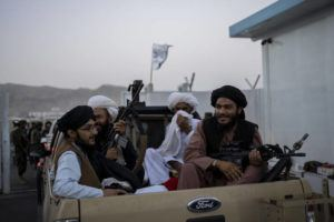 ASSOCIATED PRESS                                 Taliban fighters sit in a pickup truck at the airport in Kabul, Afghanistan, today. Some 200 foreigners, including Americans, flew out of Afghanistan on an international commercial flight from Kabul airport, the first such large-scale departure since U.S and foreign forces concluded their frantic withdrawal at the end of last month.