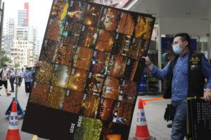 ASSOCIATED PRESS                                 Police officers take away a cardboard featuring pictures of annual candlelight vigil from the June 4th Museum as an evidence, in Hong Kong.