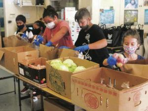 COURTESY SHELBIE KAHOLOAA                                 Hamakua Youth Center keiki pack boxes of fresh produce and locally sourced meat for the nonprofit's food assistance programs.