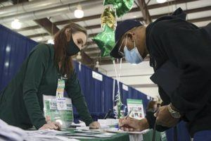 MIKE SIMONS/TULSA WORLD VIA AP                                 Chauntelle Broucker, of Dollar Tree, watches as Howard Goins fills out paperwork during an Oklahoma Employment Security Commission job fair at the Tulsa Fairgrounds Thursday in Tulsa, Okla.
