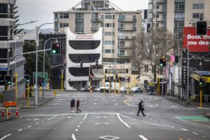 ASSOCIATED PRESS                                 People cross nearly empty streets in the central business district of Auckland, New Zealand, on Friday.