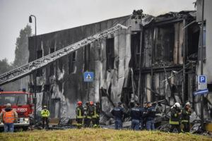 ASSOCIATED PRESS                                 Firefighters work on the site of a plane crash, in San Donato Milanese suburb of Milan, Italy, today. According to media reports, a small plane carrying six passengers and two crew members crashed into an apparently vacant office building in a Milan suburb.