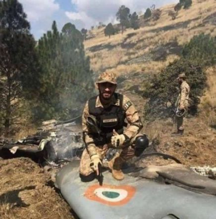 A Pakistani Soldier Sitting On The Wreckage Of A Jet Plane Of The Indian Air Force