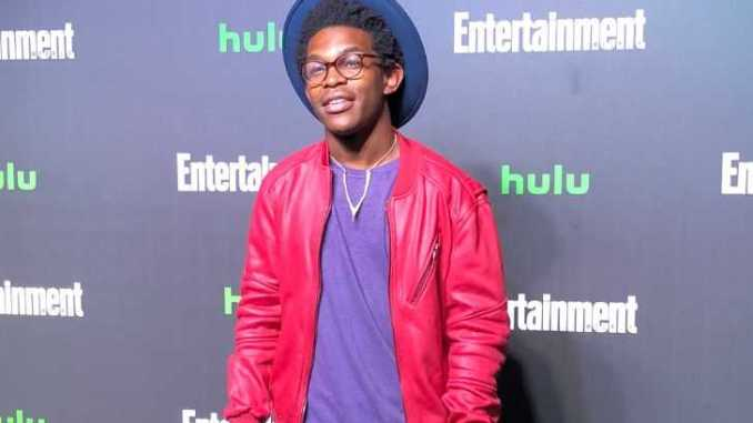 Camrus Johnson in a red jacket and blue t-shirt at a Hulu event.