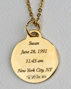 Back side of gold-colored StarCharm personalized pendant engraved with the name, birth date and time, and birthplace of the person whose astrological natal chart appears on the front side