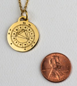 StarCharm gold-colored pendant shown next to a penny for size comparison