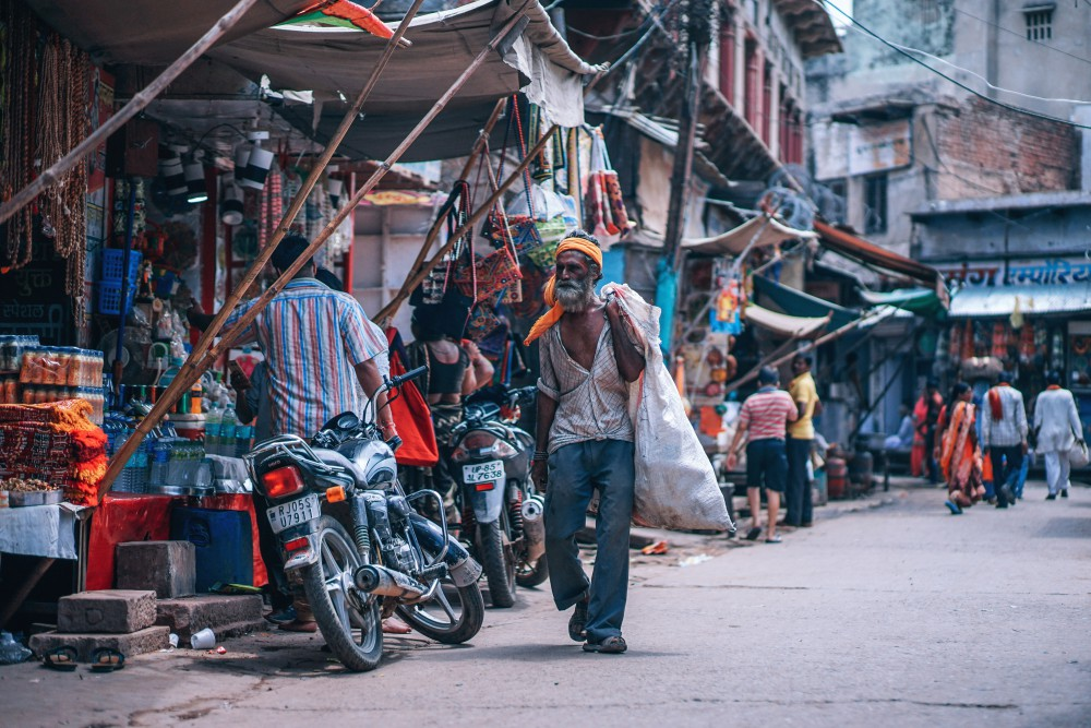 An old man walking in the slum with a sack on his back