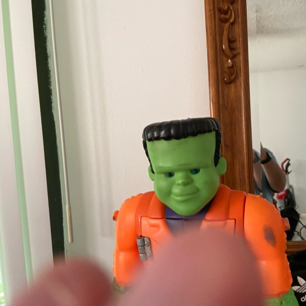Big Fran standing on a dresser with a mirror in the background. He is a Frankenstein's Monster doll with an orange suit, green face and hands.