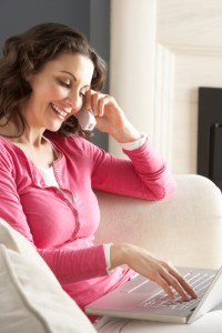 Woman Using Laptop Relaxing Sitting On Sofa At Home Talking On Phone