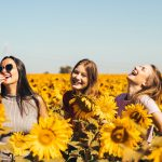 3 women smiling in a sunflower field