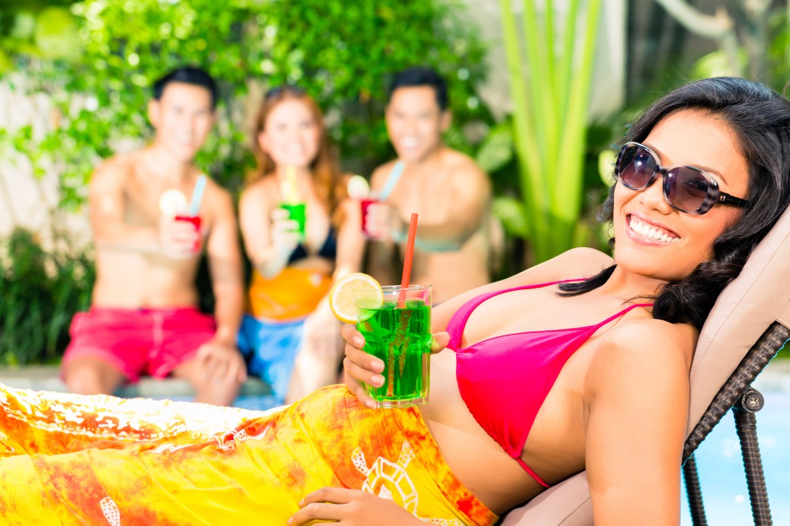 asian friends partying and drinking at vacation club