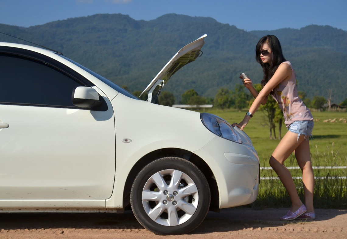 an asian woman calls for roadside assistance
