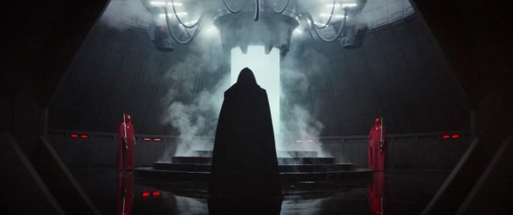En wie zien we hier in het zwart gehuld? Het is niet Darth Vader, en de bewegingen doen me ook niet denken aan Palpatine. We zien Imperial Guards op de achtergrond, dus dit personage zal wel met Palpatine te maken hebben. Hij lijkt net voor de scene overgang te knielen voor de buis (bacta tank, of energie core?) op de achtergrond.