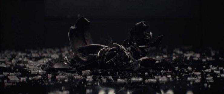 """Gedurende het volgende shot horen we Rey """"Darkness"""" antwoorden. En gepaard met dit antwoord gaan beelden van de helm van Kylo Ren. Deze is echter in slechtere staat dan die van zijn grootvader. De helm ligt in stukken op de grond, omringd door glas/transparisteel scherven. Zijn dit de resultaten van een gevecht, of een van de bekende woedeuitbarsting van Ben?"""