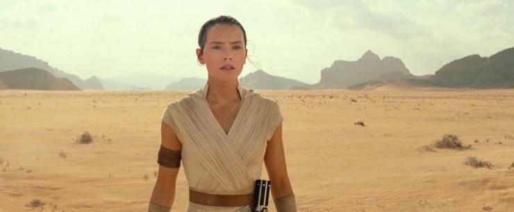 """We beginnen met het Lucasfilm logo en horen op de achtergrond Rey buiten adem hijgen. Vervolgens zien we Rey in een woestijn op adem komen en horen we de stem van Luke Skywalker zeggen dat """"ze"""" alle kennis die ze hadden doorgegeven hebben. Rey draagt een nieuwe, witte, outfit met een capuchon. Deze kleding heeft ontzettend veel weg van haar eerdere outfits, blijkbaar is ze erg content met haar eigen stijl en ik kan haar daar geen ongelijk in geven."""