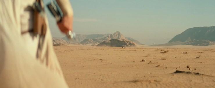 """Rey haalt het lightsaber van haar riem af (ze heeft blijkbaar ook een nieuwe methode bedacht om hem aan een riem vast te maken) terwijl Luke zegt dat er nu """"duizend generaties in Rey leven"""", doelend op alle kennis van de Jedi die nu enkel nog bij Rey bekend is. We zien Rey in de verte kijken en horen lichtjes het geluid van een aanvliegende TIE Fighter.En Luke maakt zijn zin af met """"maar dit is jouw gevecht"""" terwijl Rey de aanstormende TIE Fighter aan staart."""