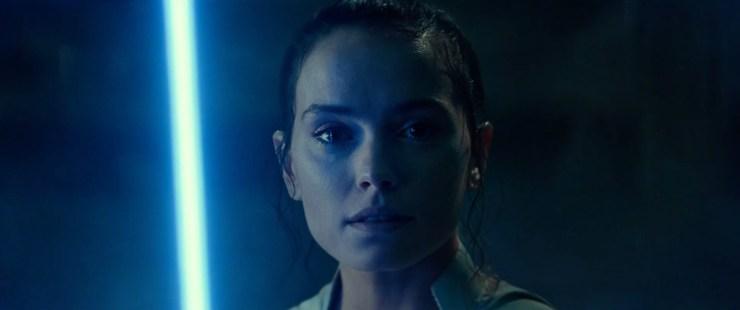 """En we sluiten deze The Rise of Skywalker trailer af met een shot van Rey met haar light saber in haar hand terwijl we Luke horen zeggen """"The Force will be with you"""" wat vervolgens door Leia wordt aangevuld met """"always""""."""