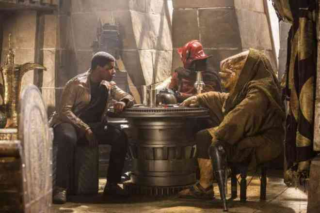 Finn, a dark-skinned human, talking to two aliens in a cantina built of stone blocks and spaceship parts. One alien looks elephantine and reptilian. The other wears a red, devil-like mask.