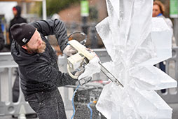 a man uses a saw to sculpt ice into a winter-themed design