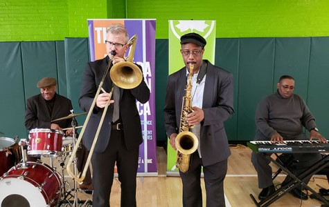 A band which includes a trombone player, saxophonist, drummer, and pianist performs indoors at a recreation center