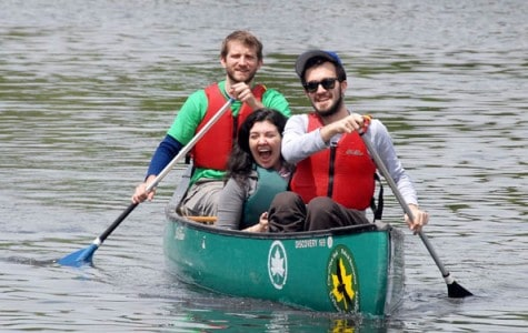 three people use a park ranger canoe on a lake