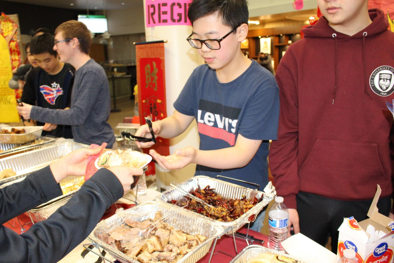 Nathen Li '20 serves a parent his mom's famous soy-braised pork.  On the side, he offered cabbage dumplings with spicy sauce.