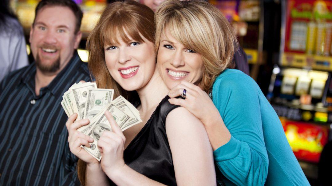 Two women hugging holding one hudred dollar bills in a fan