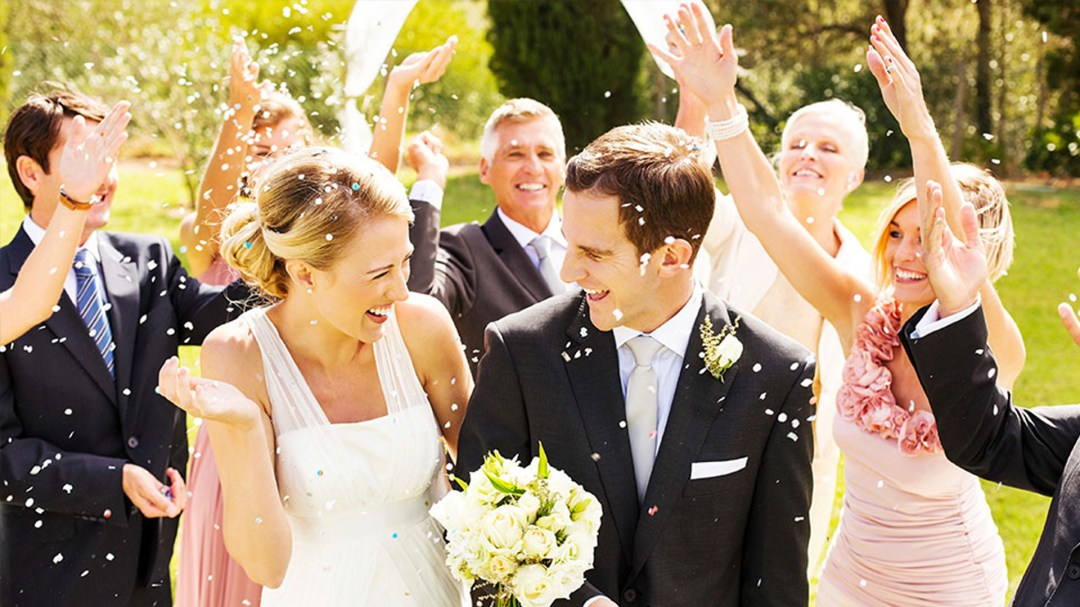 Bride and Groom walking across lawn while wedding party throws confetti